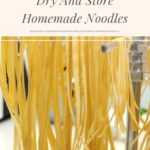 Homemade noodles hanging on a noodle drying rack.