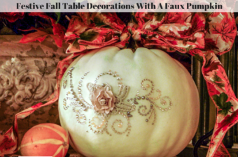 A white pumpkin decorated with a bow and bling.
