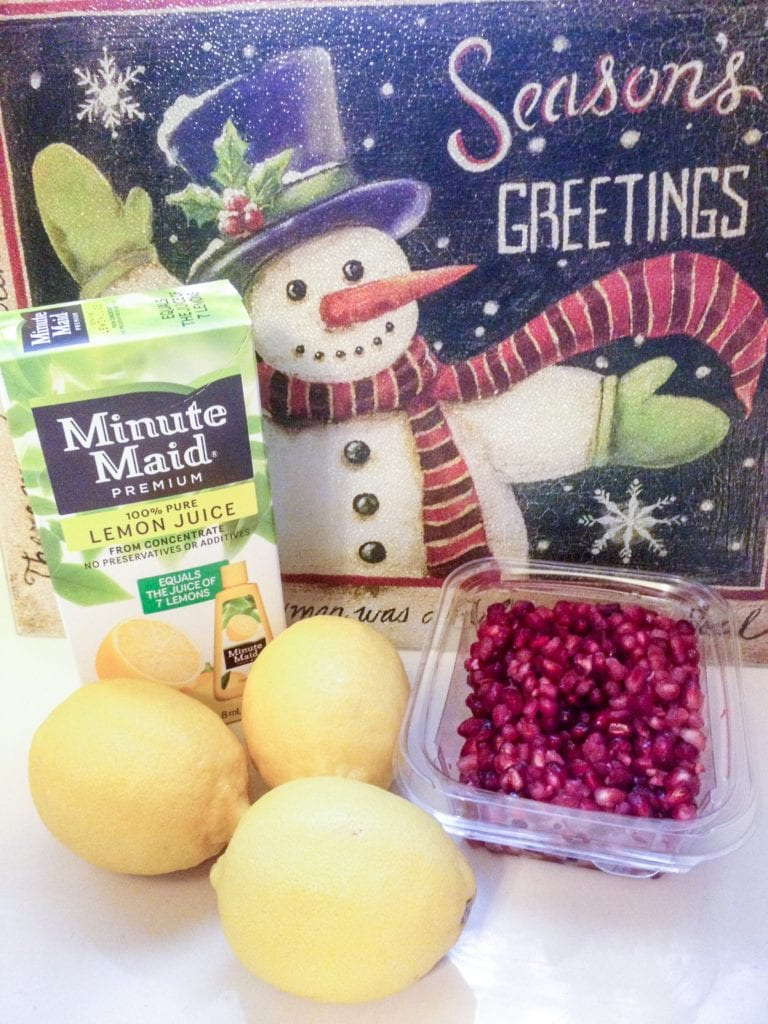 Minute Maid Lemon Juice, fresh lemons and pomegranate fruit on a countertop waiting to be made into this easy pomegranate lemonade drink recipe.