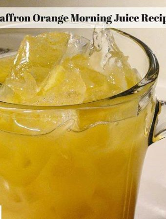 Ice in a glass filled with saffron infused orange juice.