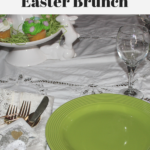 A plate, utensils and a wine glass sitting on a table decorated for Easter.