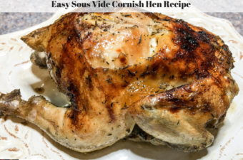 A completely cooked Cornish hen with a crisp skin resting on a plate.