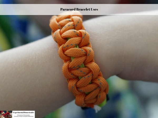 An orange paracord bracelet on a wrist.