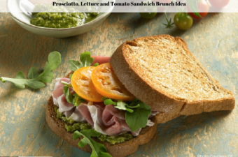 A prosciutto, lettuce and tomato sandwich on a plate with a bowl of pesto, fresh lettuce and whole tomatoes sitting off to the side.