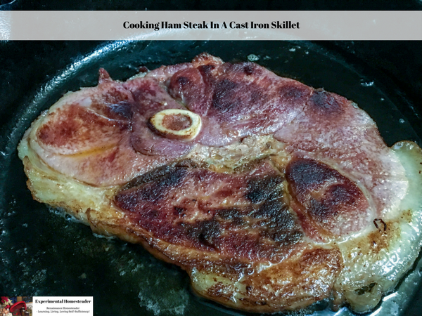 A ham steak cooking in a cast iron skillet.