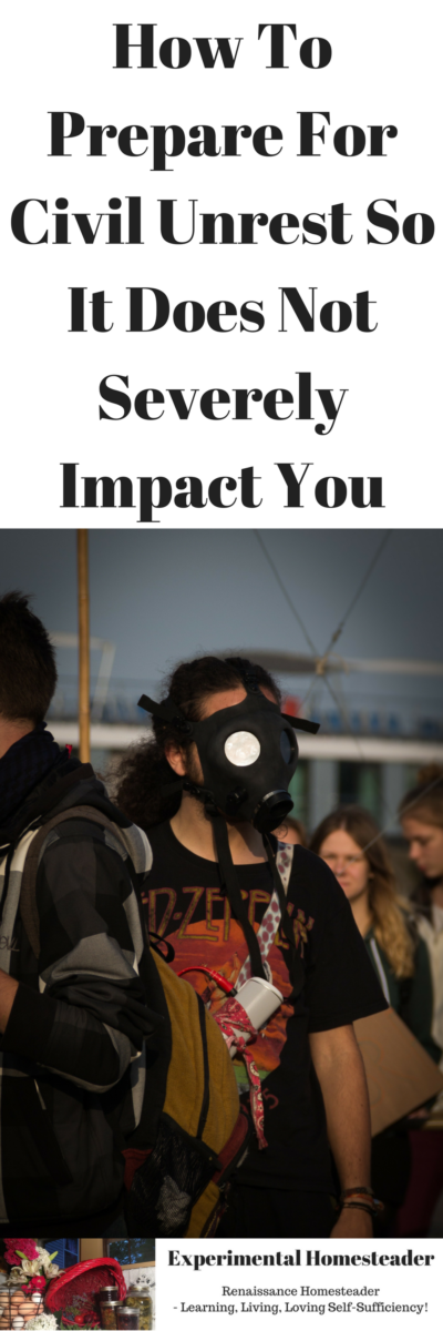 A woman in a gas mask and other people standing around her facing away from the camera.