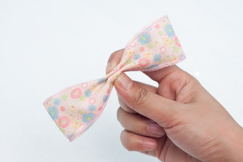 This picture shows the center of the ribbon being pinched together to create the bow.