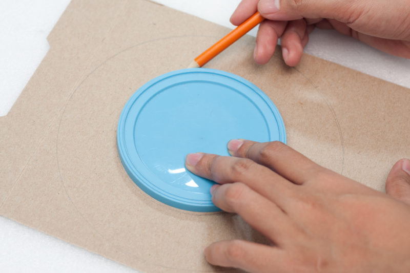 A hand using a pencil to trace around a plastic lid laying on a piece of cardboard.