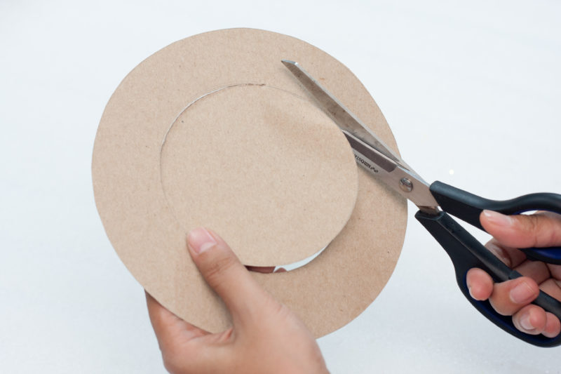 Using scissors to cut out the circles that were drawn on the cardboard.