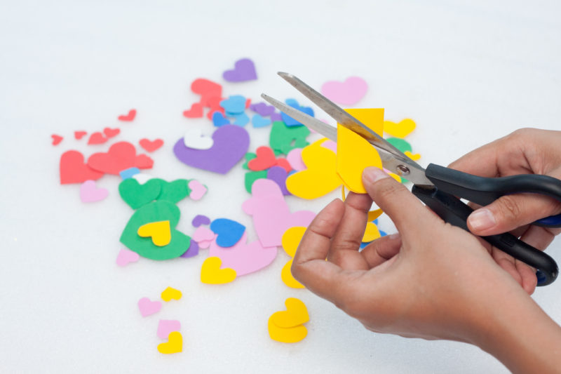 This photo shows the cutting out of multiple colored heart shapes.