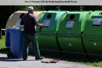 A man in front of recycle bins with his trash can filled full of recyclable material.