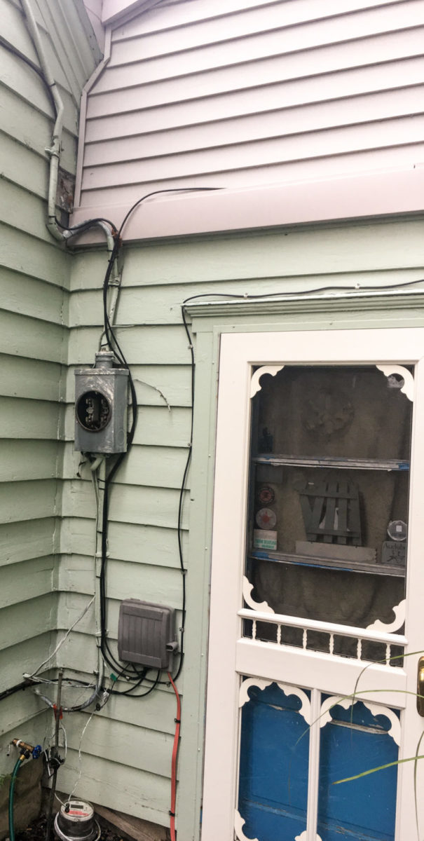 The old meter box and wiring still attached to the outside of the house.
