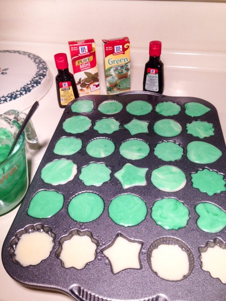 The white chocolate and the green colored white chocolate being added to the pan.
