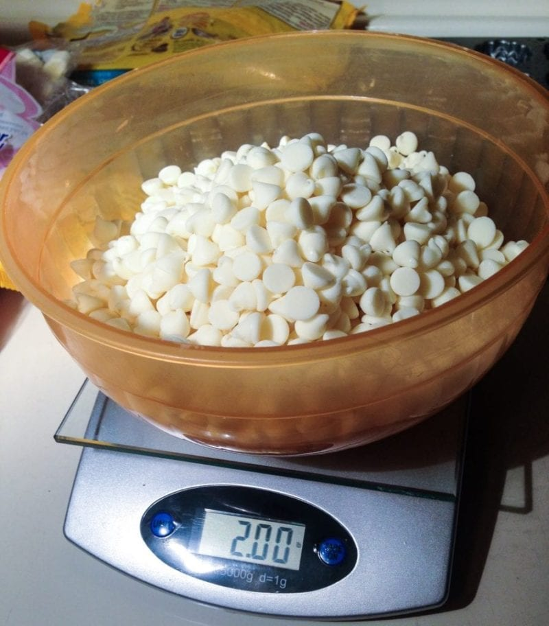 White chocolate in a bowl on top of a scale.
