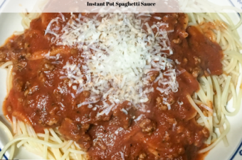 Cooked spaghetti on plate topped with homemade spaghetti sauce and freshly grated parmesan cheese.