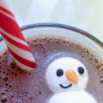 A snowman marshmallow floating in a cup of hot chocolate with a peppermint stir stick beside it.