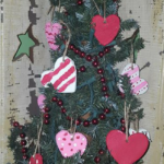An evergreen tree decorated with heart shaped ornaments and red beads.