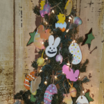 A primitive Easter tree decorated with handmade salt dough ornaments. In this photo you see a purple burlap streamer, a pink salt dough bunny rabbit head and a fake Easter egg.