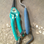 A pair of goat hoof trimmers and a hoof pick laying side by side on a table.