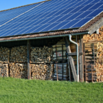 A wood shed with solar panels on top.