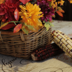 Fall flowers in a wicker basket, a couple ears of Indian corn and a mason jar with a lit candle inside all sitting on a table.