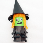 A witch made out of an empty toilet paper roll, yarn and construction paper.