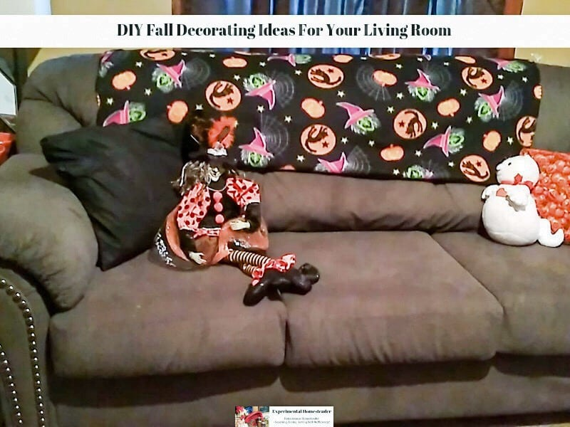 A couch with pillows, plush animals and a throw on the back,.