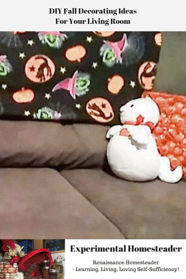A plush ghost sitting on a couch in front of a pillow.