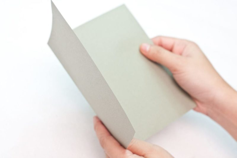The cardboard being folded to create a card.
