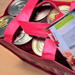 Cans of food being put into a reusable shopping bag.