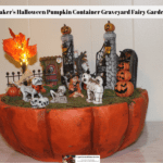 A Maker's Halloween Pumpkin Container decorated to look like a graveyard fairy garden complete with skeletons, skull animals and an LED lighted tree.