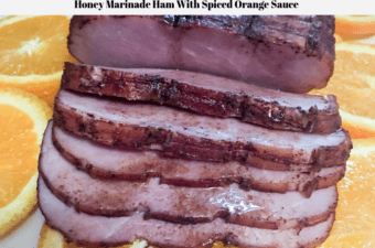 A pre-sliced Frick's Gourmet Ham With Natural Juices glazed with an orange honey sauce and sitting on a platter of orange slices.