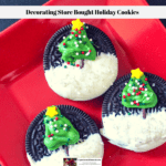 Oreo cookies decorated with a Christmas tree and candy snow on a red plate.