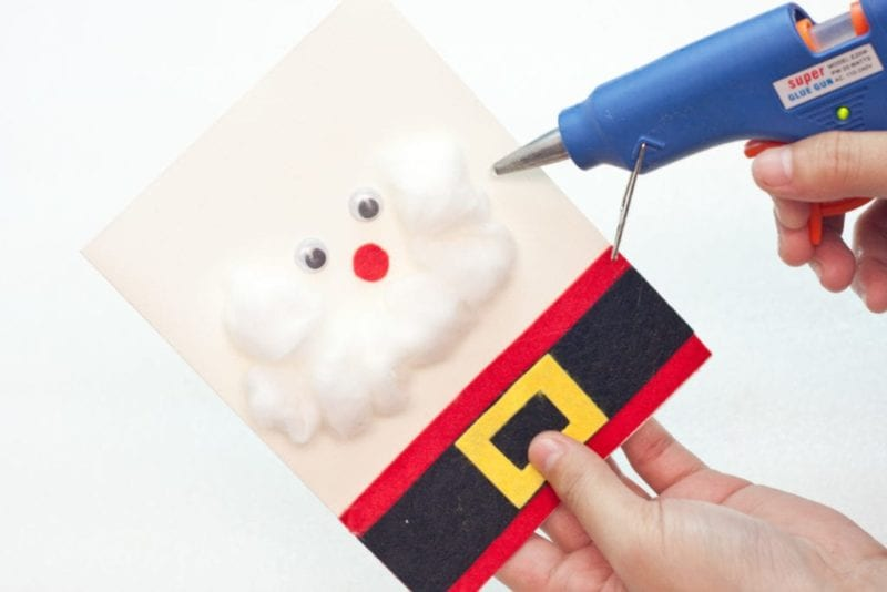 The cotton being glued on to the front of the cute handmade card to make Santa's beard.
