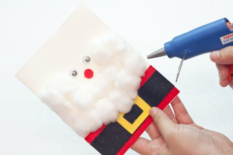 The cotton balls being glued to the side of the cute handmade card.