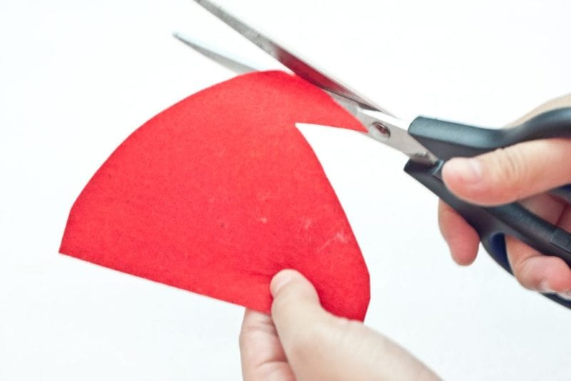Santa's hat being cut out of red felt.