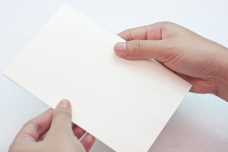 The white card stock being folded to create a greeting card.