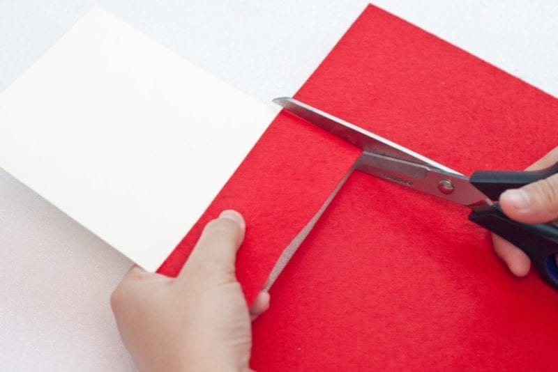 Red felt being cut for the cute handmade card.