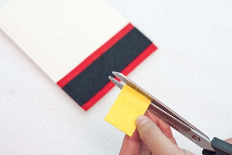 A square of yellow felt being cut.