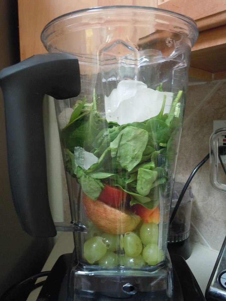 Fruits and spinach in a blender.
