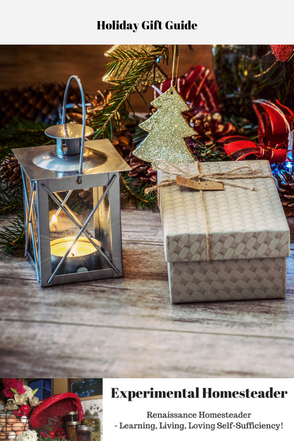 A decorative metal lantern and a present sitting in front of a Christmas tree.