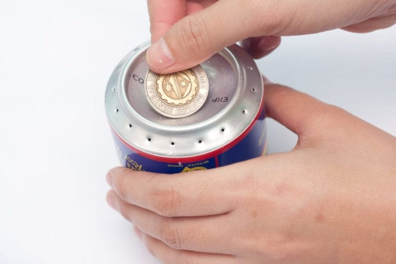 A coin being placed over the large hole in the center of the soda pop cans.