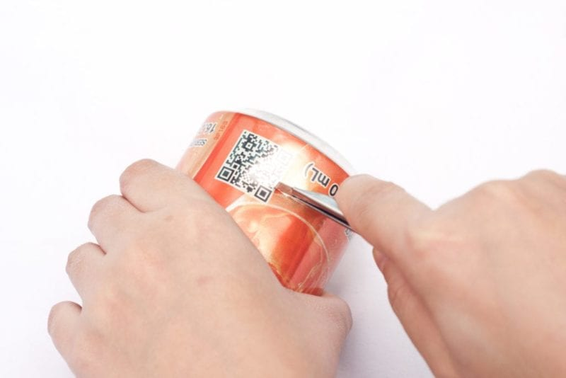 A sharp knife is being used to slice off the bottom of a soda can.