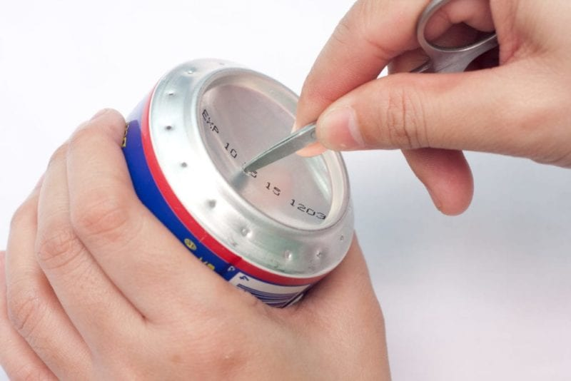 A knife being used to make a large hole in the center bottom of a soda pop can.
