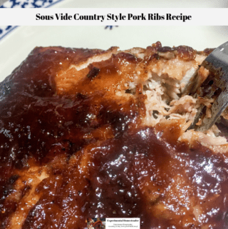 The cooked sous vide country style pork ribs with carmalized BBQ sauce on a plate with a fork inserted to break the meat apart.