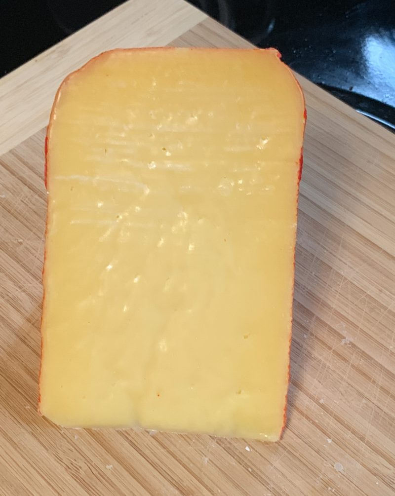 The Mehon-Menorca hard cured cheese sitting on a cutting board.