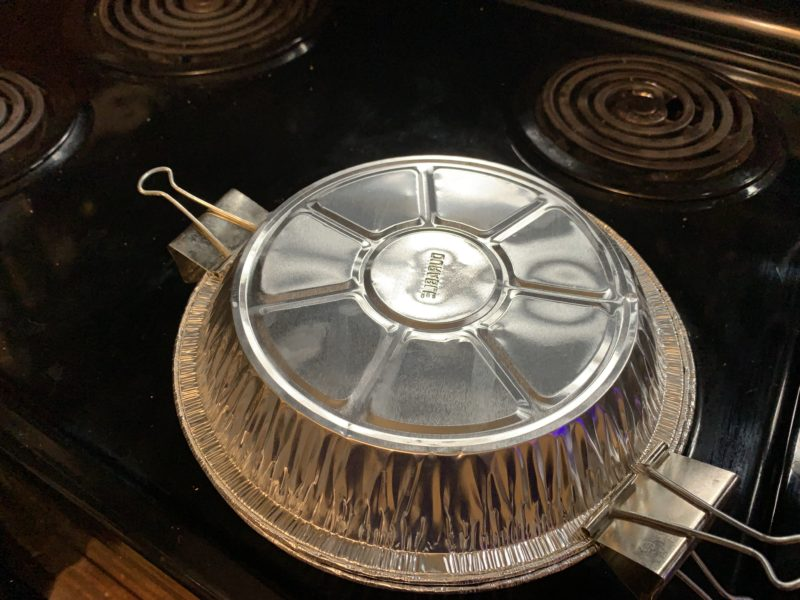 A second pie pan placed on top of the first pipe pan and secured using paper clamps.
