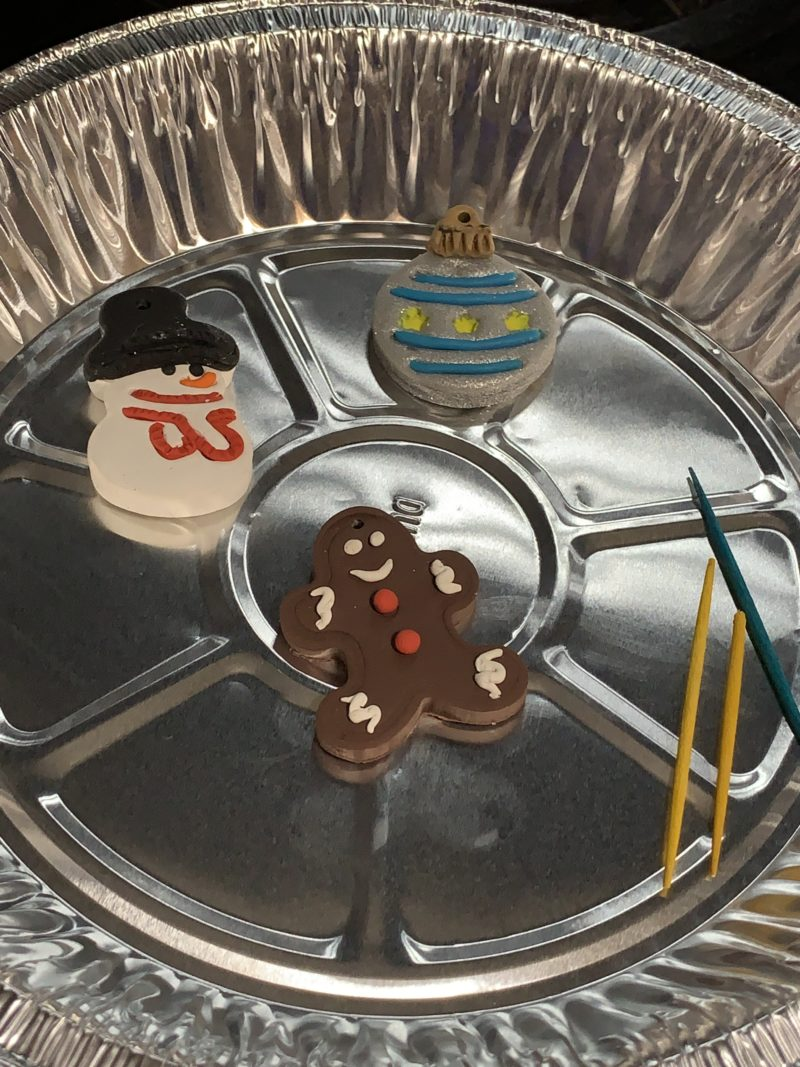 The polymer clay Christmas ornaments with the toothpicks removed cooling in the pie pan.