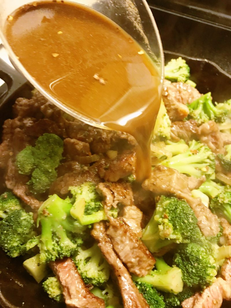 The liquid ingredients being poured over the meat and vegetables in the cast iron skillet.