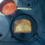 A grilled cheese sandwich cooking in a cast iron griddle on top of a wood burning stove with a pan of tomato soup on the side.